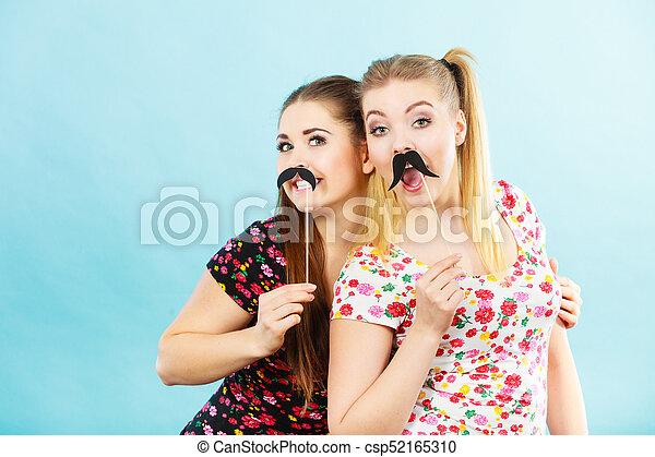 Two happy women holding fake moustache on stick - csp52165310