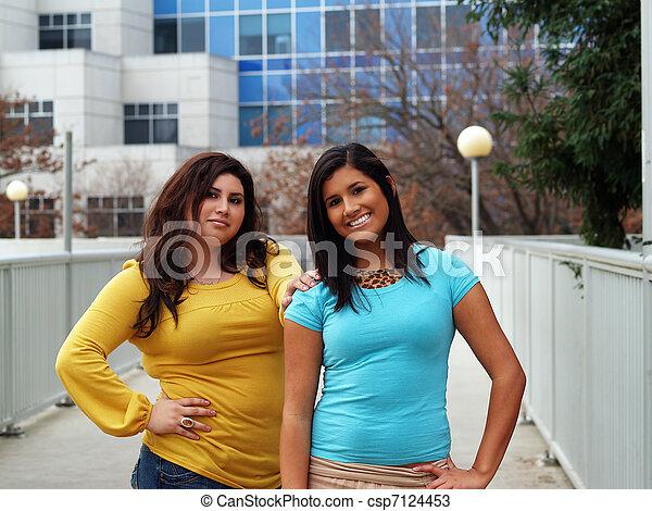 Two hispanic sisters outdoor portrait standing buildings - csp7124453
