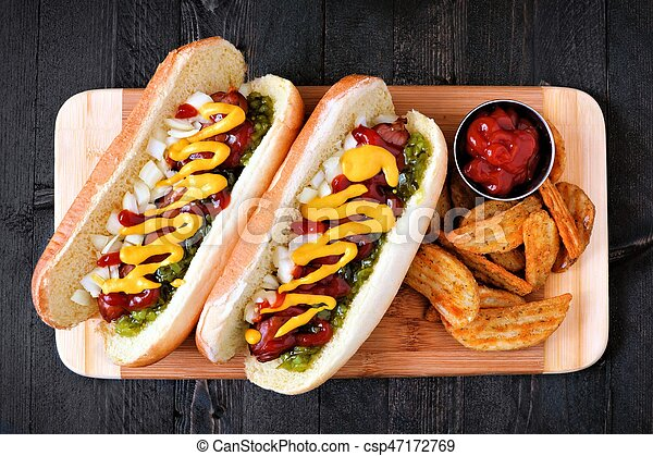 Two hot dogs fully loaded with toppings and potato wedges on wooden board, overhead view - csp47172769