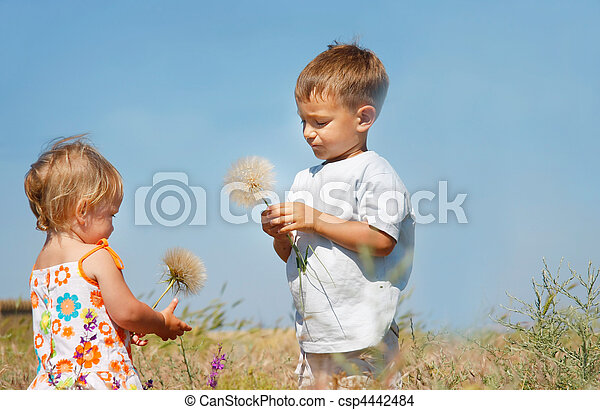 two kids playing with big dandelions - csp4442484