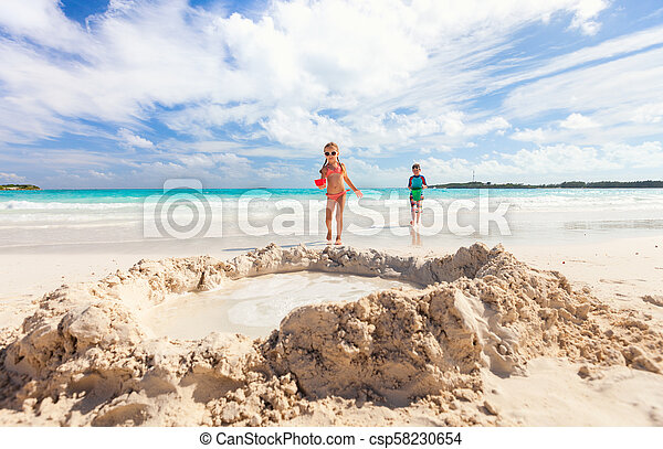 Two kids playing with sand - csp58230654
