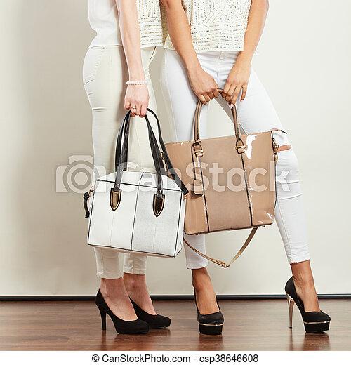 4e9da2b2a0a Two ladies holding handbags.