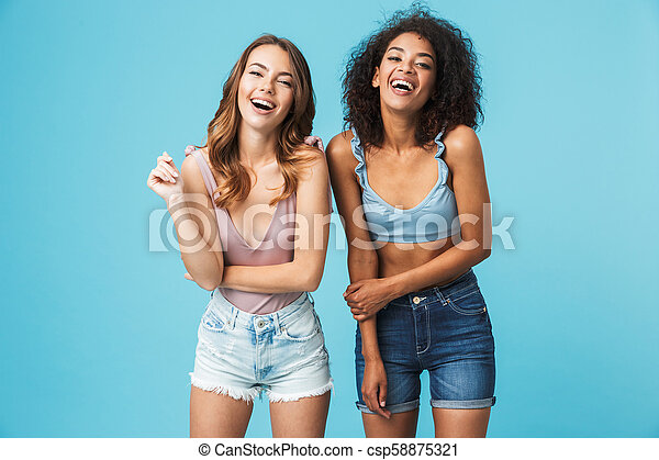 Two laughing young girls dressed in summer clothes - csp58875321