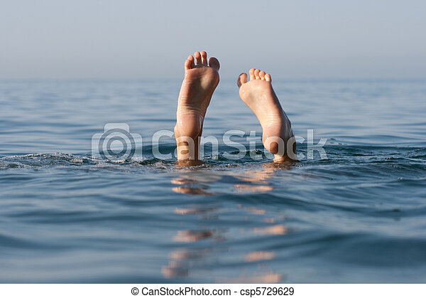 two legs on sea water still surface - csp5729629
