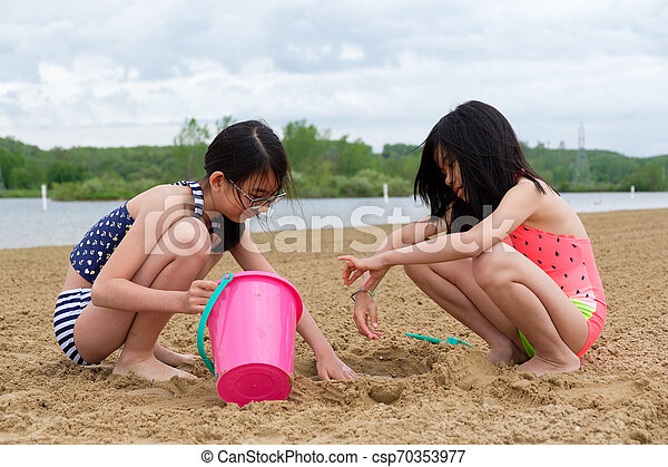 Two little Asian girls playing sand at beach - csp70353977