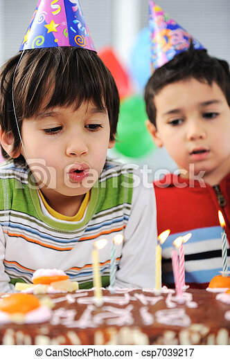 Two little boys blowing candles on cake, happy birthday party - csp7039217