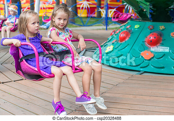 Two little cute sisters ride on carousel in the park - csp20328488