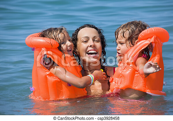 two little girls bathing in lifejackets with young woman in pool on resort - csp3928458