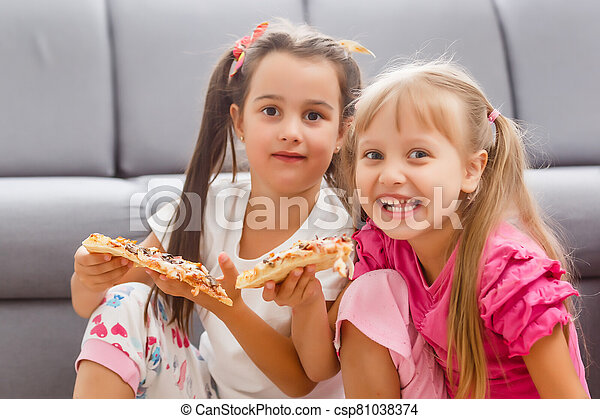 Two little girls eating huge pizza at home - csp81038374