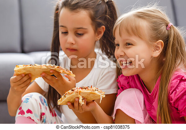 Two little girls eating huge pizza at home - csp81038375