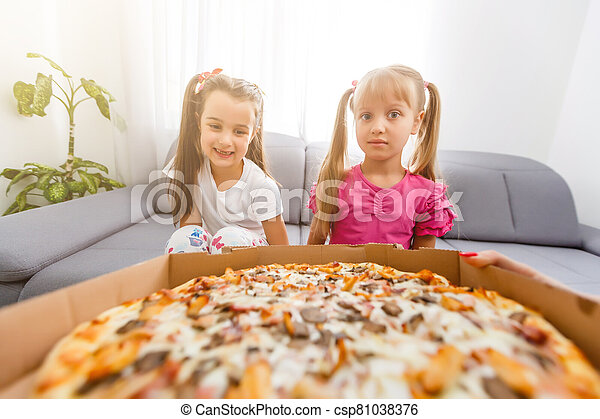 Two little girls eating huge pizza at home - csp81038376