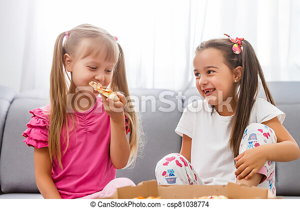 Two little girls eating huge pizza at home - csp81038774