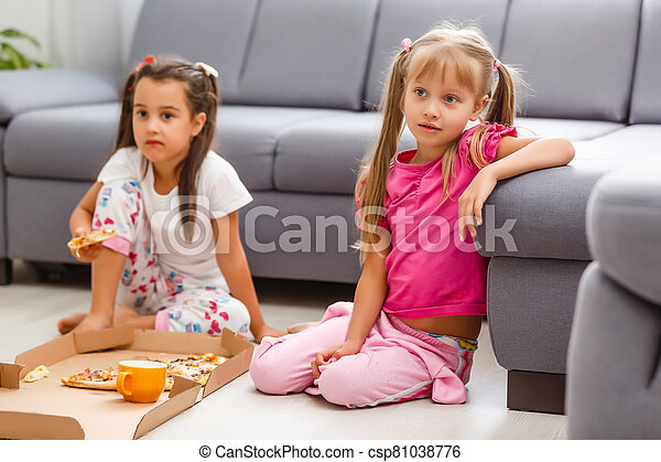 Two little girls eating huge pizza at home - csp81038776