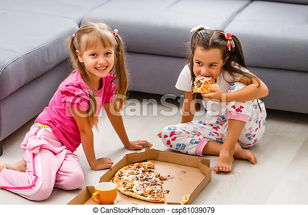 Two little girls eating huge pizza at home - csp81039079