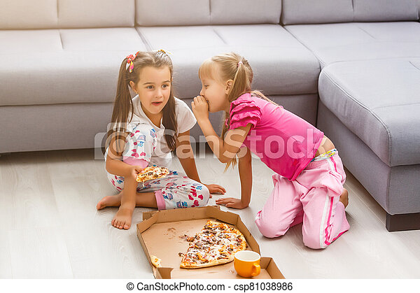 Two little girls eating huge pizza at home - csp81038986