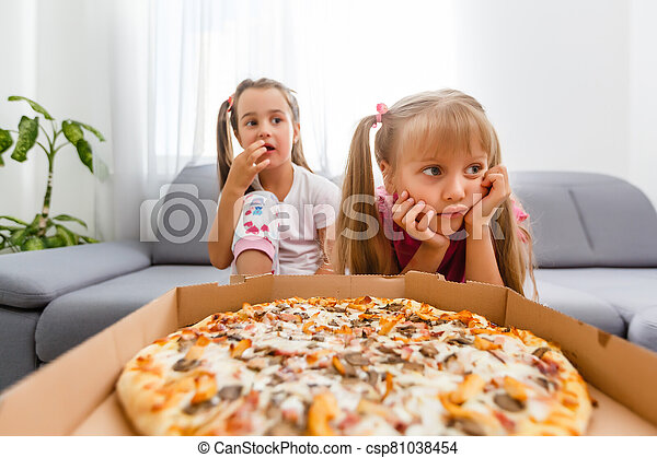 Two little girls eating huge pizza at home - csp81038454