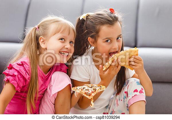 Two little girls eating huge pizza at home - csp81039294