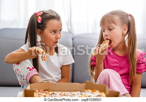 Two little girls eating huge pizza at home - csp81038501