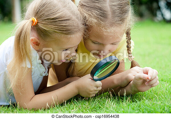 Two little girls with magnifying glass outdoors in the day time - csp16954438