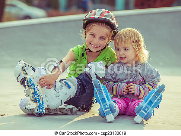 two little sisters in a roller skates  - csp23130019