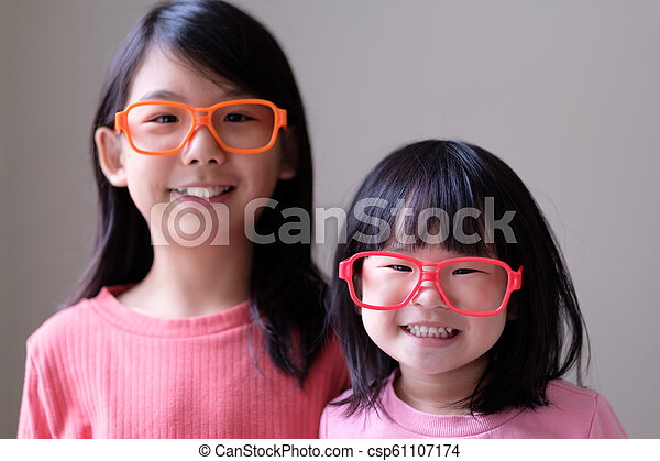 Two little sisters with big eyeglasses - csp61107174