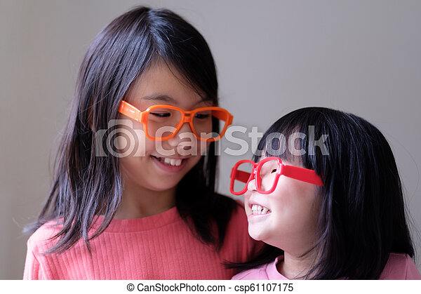 Two little sisters with big eyeglasses - csp61107175