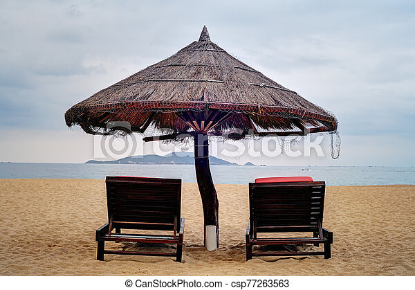 Two loungers under straw parasol at the beach - csp77263563