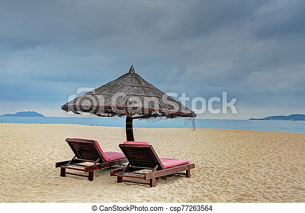 Two loungers under straw parasol at the beach - csp77263564