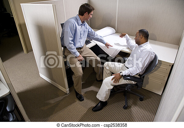 Two male colleagues working in cubicle with blueprints - csp2538358