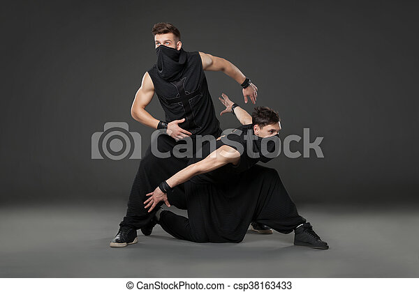 Two male dancers posing in ninja costumes on dark gray background. - csp38163433