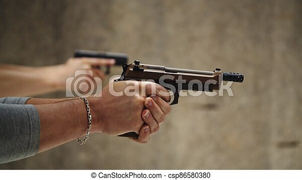 Two men are practicing shooting with hand pistol at the shooting range - csp86580380