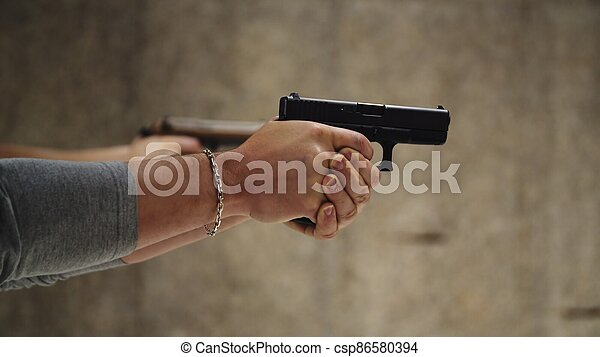 Two men are practicing shooting with hand pistol at the shooting range - csp86580394