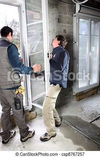 Two men fitting new window - csp8767257