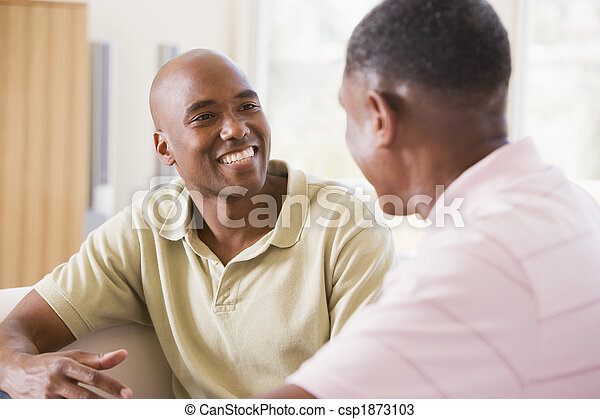 Two men in living room talking and smiling - csp1873103