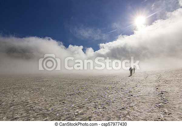 two men on snowy field in kamchatka mountains with clouds and sky above - csp57977430