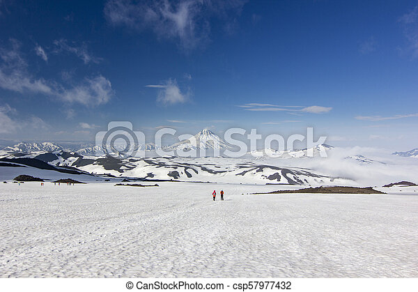 two men on snowy field in kamchatka mountains near covered by snow volcanoes - csp57977432