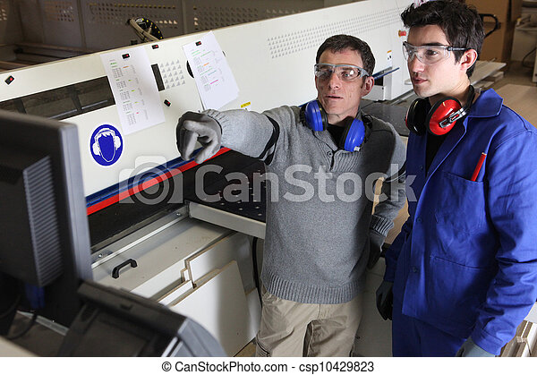 Two men operating factory machine - csp10429823