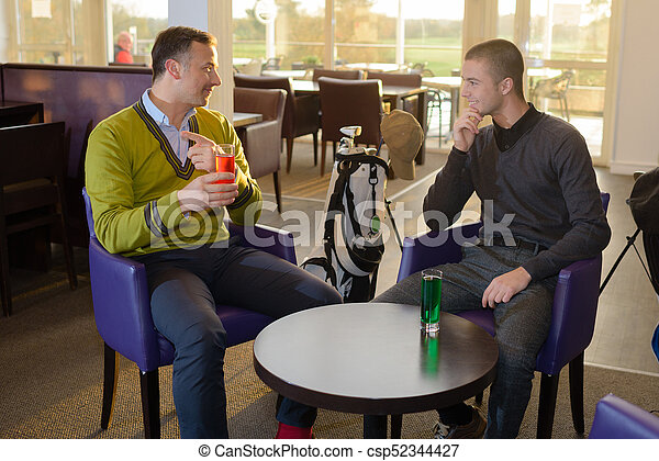 Two men sat in a bar having a drink - csp52344427