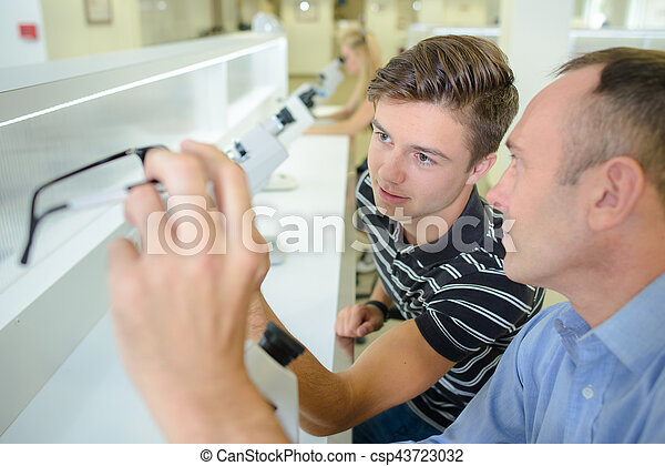 Two men with eyeglasses and microscopes - csp43723032