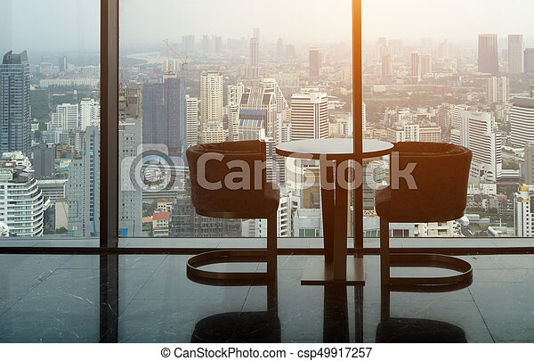 Two modern chair and circle glass table on tower office room with ...