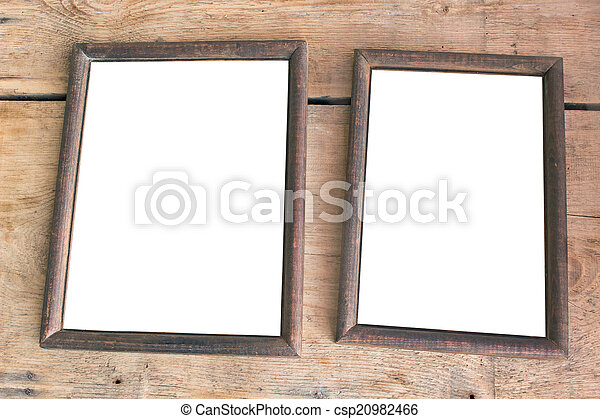 Two old photo frames on wooden background.