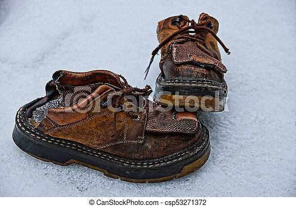 two old ragged brown boots on the snow - csp53271372