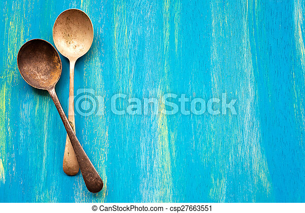 Two Old vintage spoons on blue wooden background, top view - csp27663551