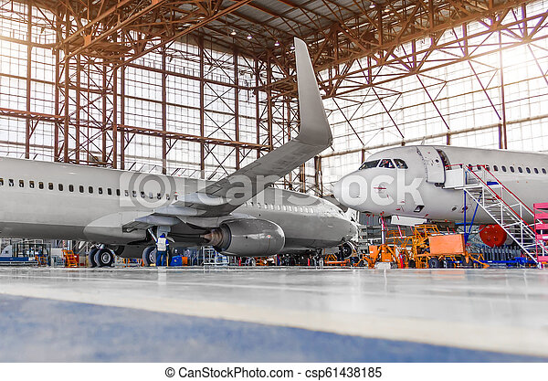 Two passenger aircraft for maintenance and repair in the hangar. - csp61438185