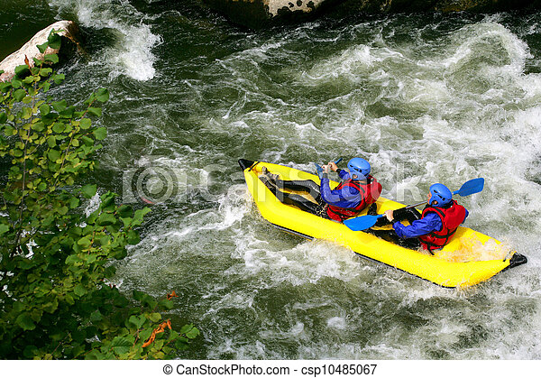 Two people kayaking down river rapids - csp10485067