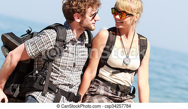 Two people tourists hiking by sea ocean. - csp34257784