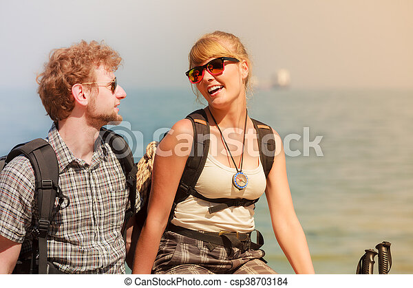 Two people tourists hiking by sea ocean. - csp38703184
