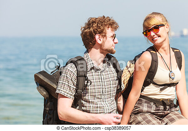 Two people tourists hiking by sea ocean. - csp38389057