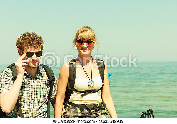 Two people tourists hiking by sea ocean. - csp35549939