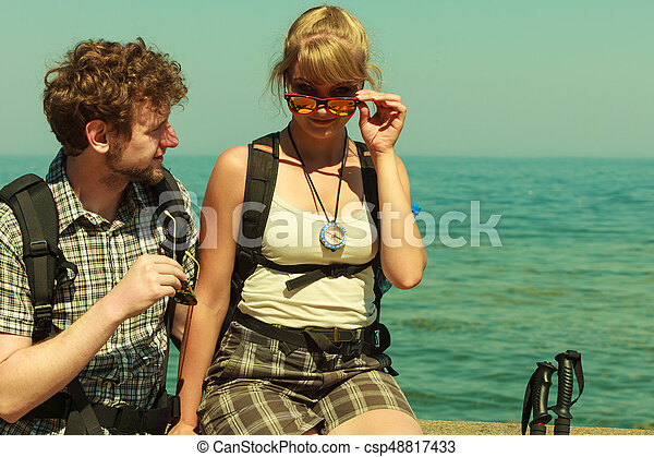 Two people tourists hiking by sea ocean. - csp48817433